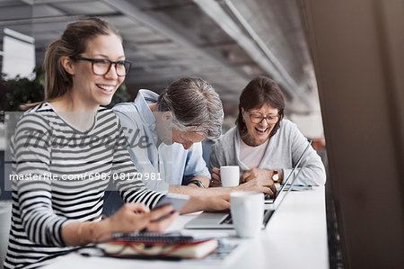 Happy business people sitting at counter in office Stock Photo - Premium Royalty-Free, Image code: 698-08170981