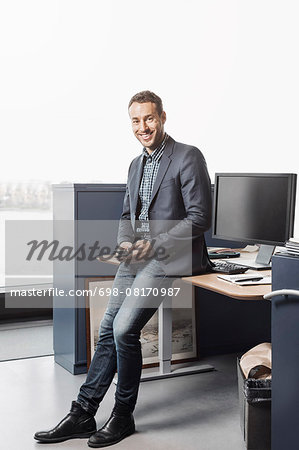 Full length portrait of confident businessman leaning on desk in office Stock Photo - Premium Royalty-Free, Image code: 698-08170987