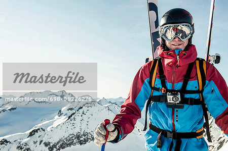 Portrait of smiling male skier standing on snowcapped mountain against clear sky Stock Photo - Premium Royalty-Free, Image code: 698-08226276