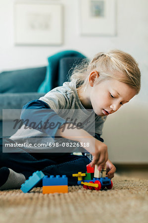 Girl making toy car with blocks while sitting on floor at home Stock Photo - Premium Royalty-Free, Image code: 698-08226318