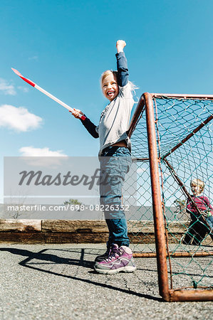 Low angle view of successful girl holding hockey stick against blue sky Stock Photo - Premium Royalty-Free, Image code: 698-08226332