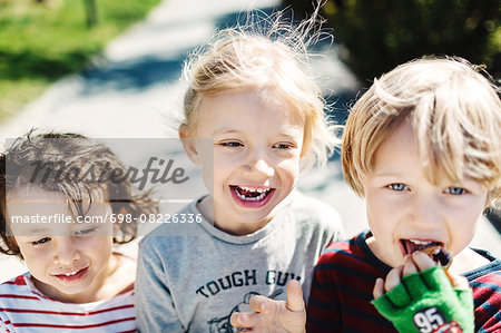 Portrait of happy boy eating ice cream while walking with friends at yard Stock Photo - Premium Royalty-Free, Image code: 698-08226336