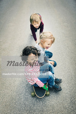 High angle view of children enjoying while sitting on skateboard Stock Photo - Premium Royalty-Free, Image code: 698-08226350