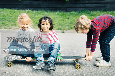 Portrait of happy children sitting on skateboard while friend pulling it at yard Stock Photo - Premium Royalty-Free, Image code: 698-08226354