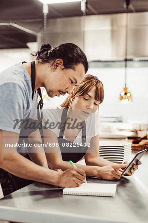 Chefs using digital tablet while writing recipe at commercial kitchen counter