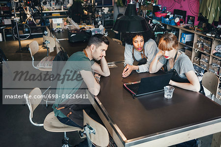High angle view of mechanics using laptop at table in workshop Stock Photo - Premium Royalty-Free, Image code: 698-08226411
