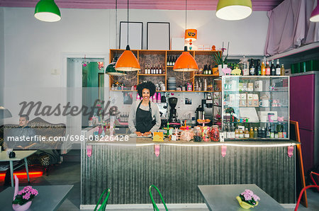 Portrait of confident female barista at cafe counter Stock Photo - Premium Royalty-Free, Image code: 698-08226428