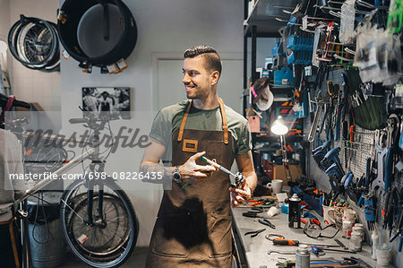Smiling male mechanic looking at colleague while repairing pedal in workshop Stock Photo - Premium Royalty-Free, Image code: 698-08226435