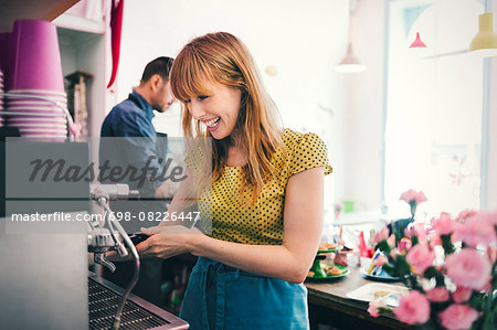 Happy barista using coffee maker in cafe Stock Photo - Premium Royalty-Free, Image code: 698-08226447