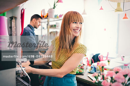 Happy female barista looking away while using coffee maker in café