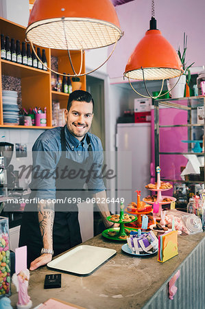 Portrait of confident male barista standing at counter Stock Photo - Premium Royalty-Free, Image code: 698-08226449