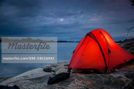 Tent on rock at lakeshore during dusk Stock Photo - Premium Royalty-Free, Image code: 698-08226492
