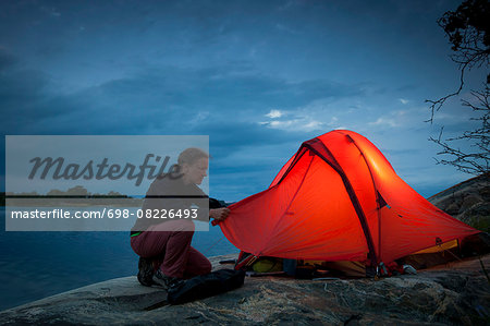 Woman fixing tent at lakeshore during dusk Stock Photo - Premium Royalty-Free, Image code: 698-08226493
