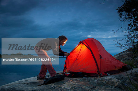 Woman looking into tent at lakeshore during dusk Stock Photo - Premium Royalty-Free, Image code: 698-08226494