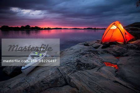 Tent and kayak at lakeshore during sunset Stock Photo - Premium Royalty-Free, Image code: 698-08226497