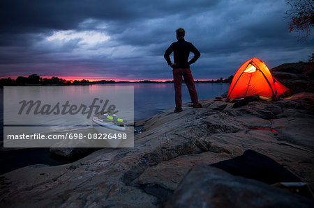 Silhouette woman standing with hands on hips by tent at campsite Stock Photo - Premium Royalty-Free, Image code: 698-08226498