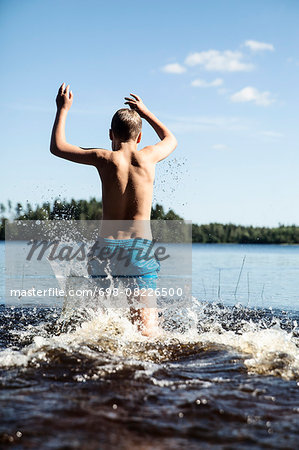 Rear view of boy running in lake Stock Photo - Premium Royalty-Free, Image code: 698-08226500