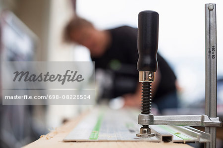 Clamp on wooden plank with female carpenter working in background Stock Photo - Premium Royalty-Free, Image code: 698-08226504