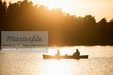 Silhouette father and son traveling in canoe on lake during sunset Stock Photo - Premium Royalty-Free, Image code: 698-08226512