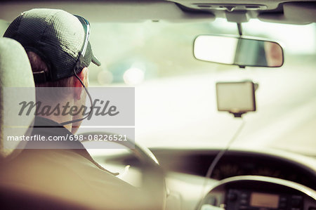 Rear view of man driving car Stock Photo - Premium Royalty-Free, Image code: 698-08226521