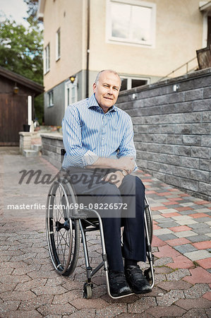Portrait of confident man sitting in wheelchair on street Stock Photo - Premium Royalty-Free, Image code: 698-08226572