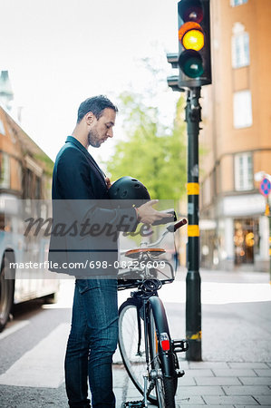 Side view of businessman using mobile phone while standing with bicycle on city street Stock Photo - Premium Royalty-Free, Image code: 698-08226609