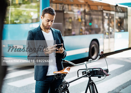 Businessman using mobile phone while standing with bicycle on city street Stock Photo - Premium Royalty-Free, Image code: 698-08226610