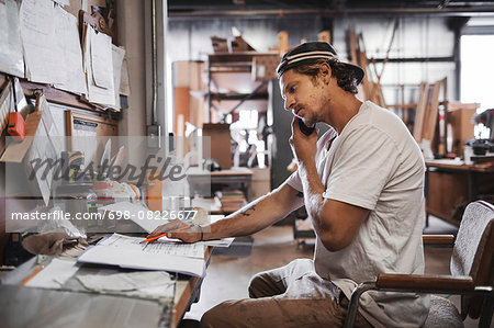Side view of carpenter using mobile phone while reading document in workshop