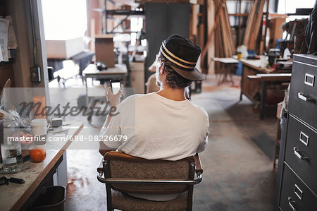 Rear view of carpenter using smart phone in workshop Stock Photo - Premium Royalty-Free, Image code: 698-08226679