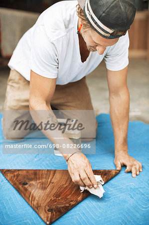 Carpenter polishing triangle shaped wood at workshop Stock Photo - Premium Royalty-Free, Image code: 698-08226696