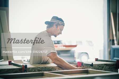 Side view of carpenter making furniture in factory Stock Photo - Premium Royalty-Free, Image code: 698-08226717