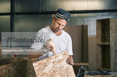 Carpenter applying glue on wooden plank at workshop