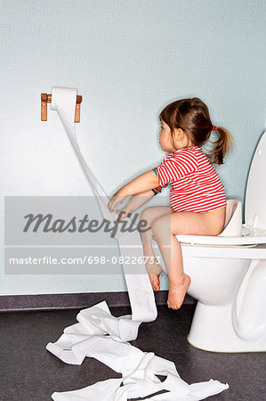 Side view of girl removing paper while sitting on toilet Stock Photo - Premium Royalty-Free, Image code: 698-08226733