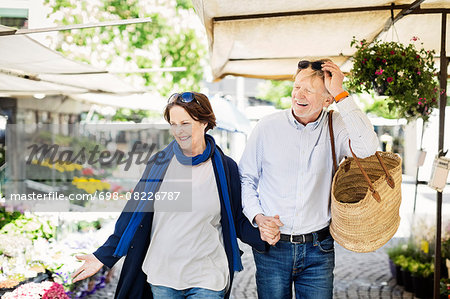 Happy senior couple walking at flower market Stock Photo - Premium Royalty-Free, Image code: 698-08226787
