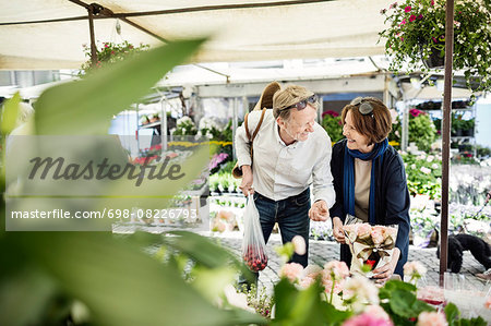 Happy senior couple talking while buying flowers at market Stock Photo - Premium Royalty-Free, Image code: 698-08226793