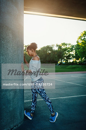 Woman stretching by column on street Stock Photo - Premium Royalty-Free, Image code: 698-08330724