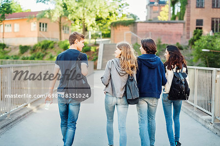 Rear view of teenagers talking while walking on bridge in city