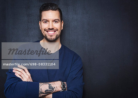 Portrait of happy businessman standing arms crossed against wall Stock Photo - Premium Royalty-Free, Image code: 698-08331104