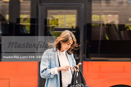 Young woman using mobile phone against bus Stock Photo - Premium Royalty-Free, Image code: 698-08393196