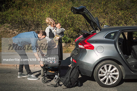 Mid adult parents with son and baby carriage near car on street Stock Photo - Premium Royalty-Free, Image code: 698-08393251