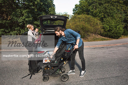 Mid adult parents with baby boy and stroller near car on street Stock Photo - Premium Royalty-Free, Image code: 698-08393253
