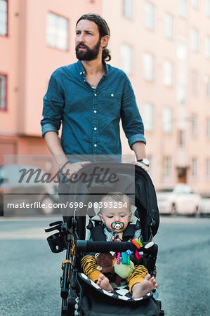 Mid adult man pushing baby in carriage on sidewalk Stock Photo - Premium Royalty-Free, Image code: 698-08393254