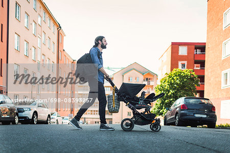Full length side view of man pushing baby in carriage crossing city street Stock Photo - Premium Royalty-Free, Image code: 698-08393257