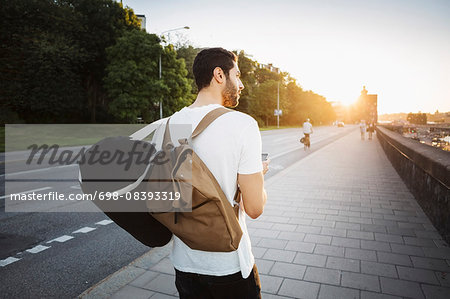 Rear view of male tourist looking away while walking on sidewalk of bridge