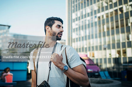 Male tourist looking away while standing in city