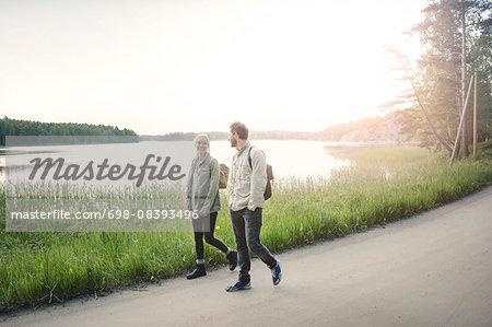 Full length of happy wonderlust couple walking on road by lake against clear sky