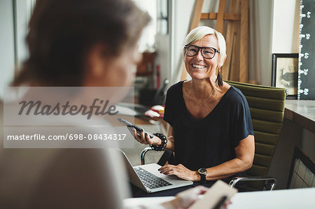Happy industrial designer holding solar product while discussing with colleague at home office Stock Photo - Premium Royalty-Free, Image code: 698-08434317