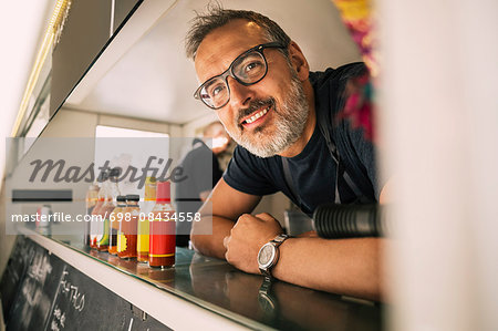 Portrait of happy male chef leaning on counter at food truck Stock Photo - Premium Royalty-Free, Image code: 698-08434558