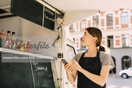 Female chef using mobile phone while looking at menu on food truck