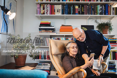 Senior couple using mobile phone at home Stock Photo - Premium Royalty-Free, Image code: 698-08545137